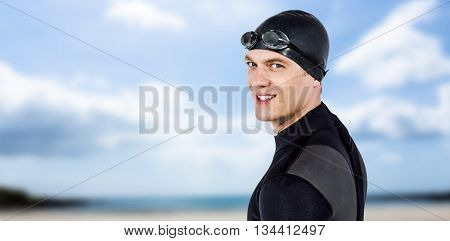 Close-up of confident swimmer in wetsuit against beach with blue sky