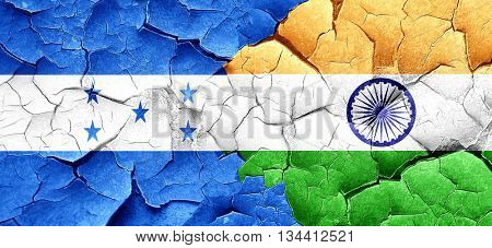 Honduras flag with India flag on a grunge cracked wall