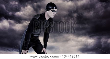 Swimmer in wetsuit and swimming goggles against gloomy sky