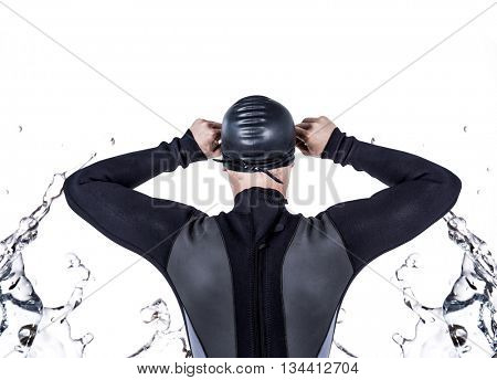 Rear view of swimmer in wetsuit wearing swimming goggles against water bubbling on white surface