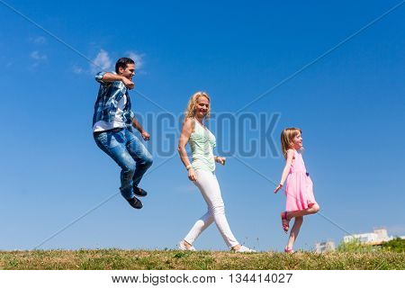 Family walks in a row, father jumping around, total view