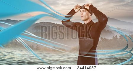 Swimmer in wetsuit wearing swimming goggles against trees and mountain range against cloudy sky