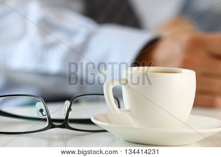 Cup of morning coffee and glasses on worktable with businessman working on background. Business meeting coffee break freelance or long hours at work concept.