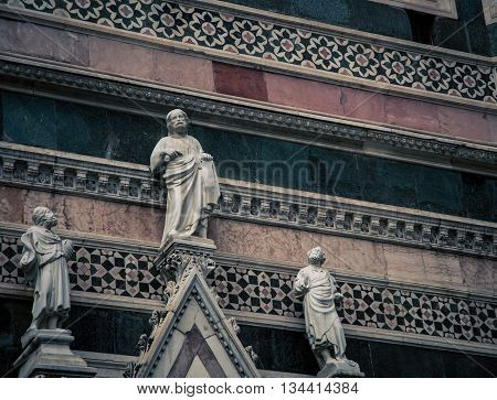 Three religious statues on a cathedral in Florence Italy