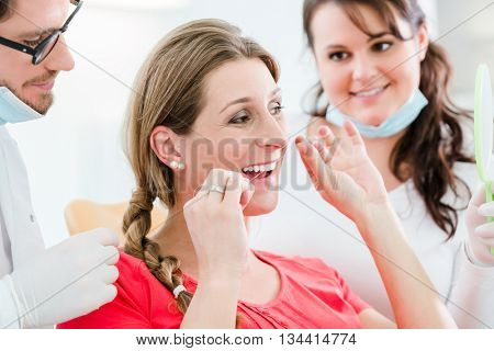 Woman at dentist using dental floss, the doctor explaining proper use