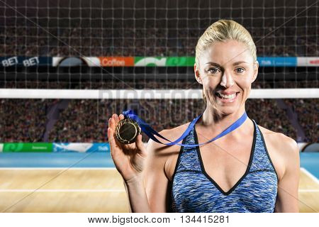 Female athlete posing with gold medal around his neck against composite image of outdoor playing field