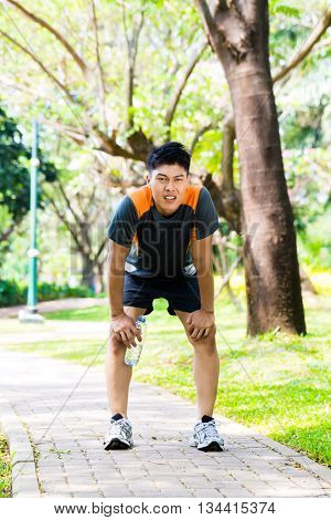 Asian man is out of breath after jogging in city park