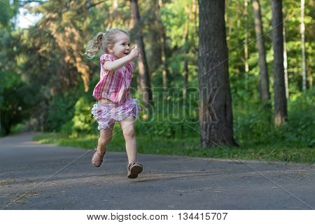 Exited three years old runner girl on asphalt park footpath is holding piece of sidewalk chalk