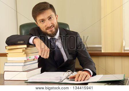 successful business man in the office with books and documents