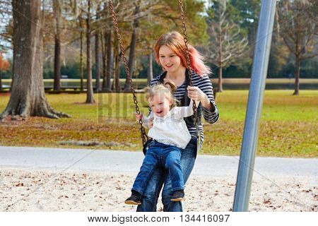 Mother and daughter in a swing having fun at the park playground