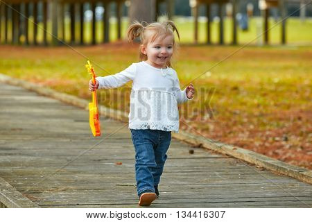 Kid baby girl with toy guitar walking fun in the autumn park