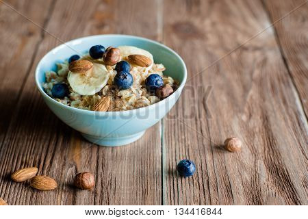Breakfast with oat porridge with berries and nuts. Porridge in blue bowl on brown wood table. horizontal, colorfull