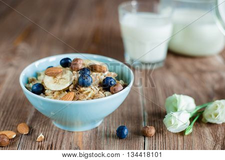 Breakfast with oat porridge with berries and nuts. milk porridge in blue bowl on brown wood table and jug with milk on a background . horizontal, colorfull, rustic style