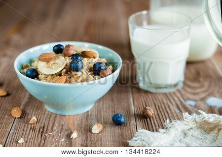 Breakfast with oat porridge with berries and nuts. milk porridge in blue bowl and glass with milk on brown wood table . horizontal, colorfull. rustic style