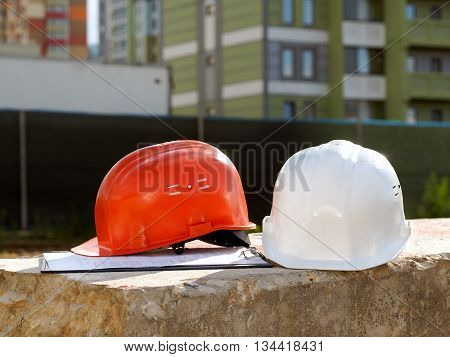 Orange helmet builder and a white helmet engineer on the background buildings. Helmets lie on a concrete block.