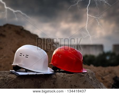 Orange helmet builder and a white helmet Engineer lying on a concrete block on a background of mountains of sand. Bad weather evening lightning in the sky.