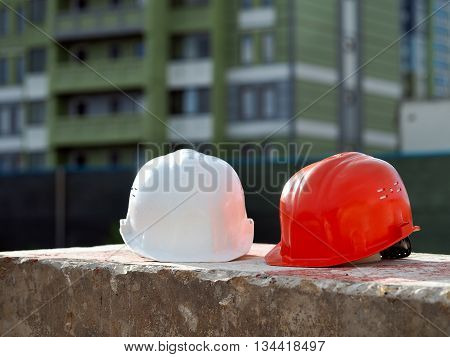 Orange helmet builder and a white helmet engineer on the background buildings. Helmets lie on a concrete block.
