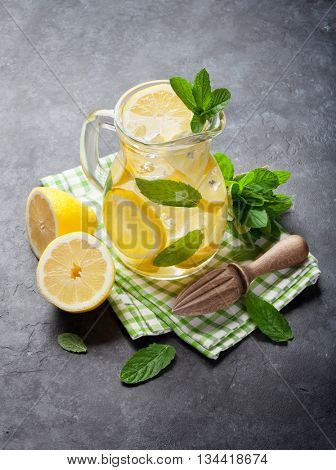 Lemonade pitcher with lemon, mint and ice on stone table