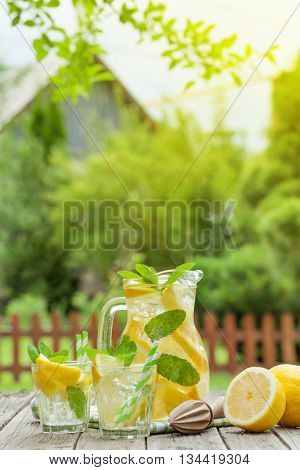 Lemonade pitcher and glasses with lemon, mint and ice on garden table