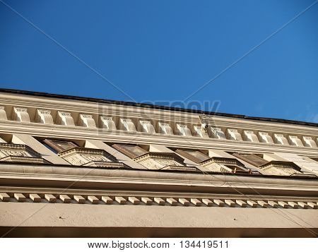 Details of archiiitectural decor of stone facade of classical building with ornaments and reliefs against blue sky