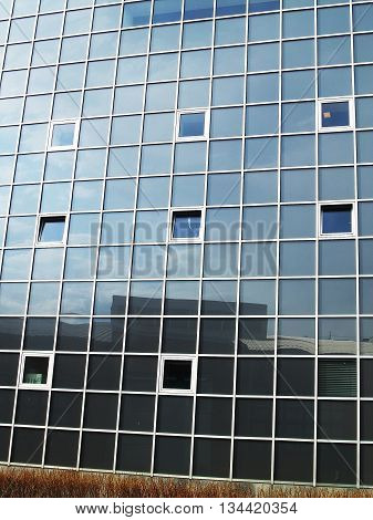 Glass wall of a building with big squre mirror windows at natural lightning. Reflections of sky and surrounding in glass windows
