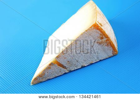 piece of light swiss cheese on blue board
