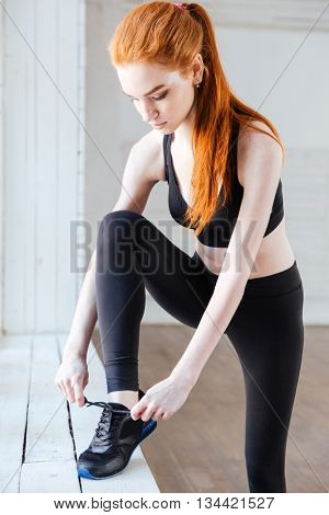 Close-up portrait of pretty young woman tying shoelaces in the gym