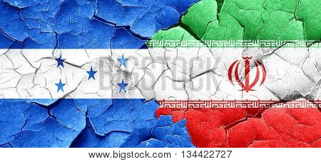 Honduras flag with Iran flag on a grunge cracked wall