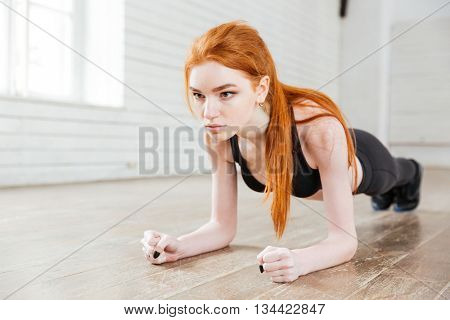 Concentrated beautiful fitness girl in sportwear exercising doing a plank in the gym
