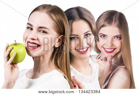 Young women with teeth braces and healthy smile eats green apple isolated on white