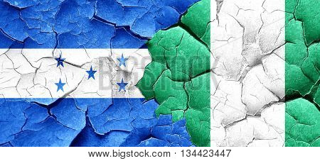 Honduras flag with Nigeria flag on a grunge cracked wall