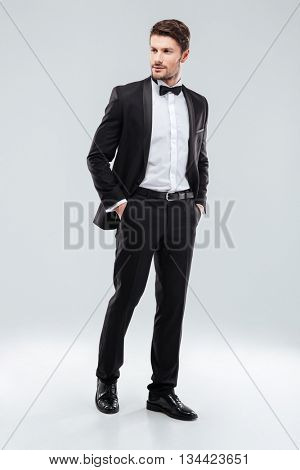 Full length of confident attractive young man in tuxedo standing over white background