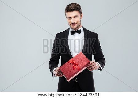 Confident attracive young man in tuxedo standing and holding gift box over white background