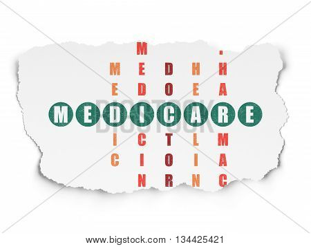 Health concept: Painted green word Medicare in solving Crossword Puzzle on Torn Paper background
