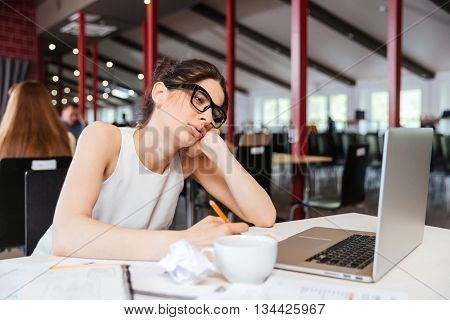 Pretty bored young businesswoman working using laptop in office