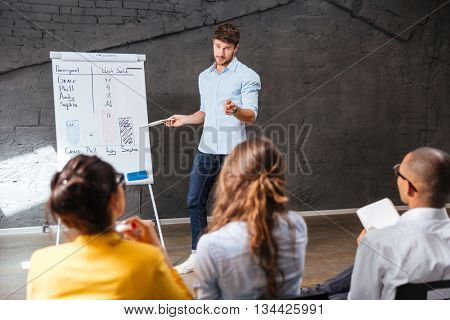 Confident handsome young businessman making presentation using whiteboard in office
