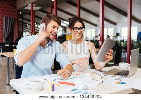 Happy beautiful young businesspeople talking on cell phone and using tablet in office together