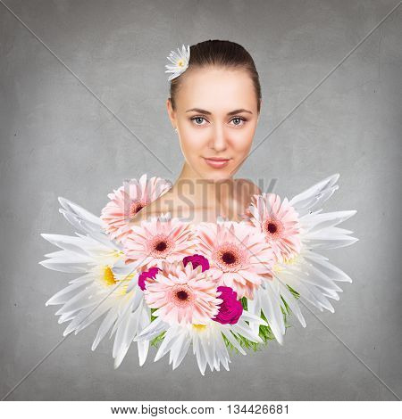 Young attractive woman with clean skin appears from bouquet flowers over gray background