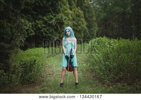 Young Girl With Blue Hair Holding Violin In Blue Dress In Spring In Park With Copy Space. Female Vio