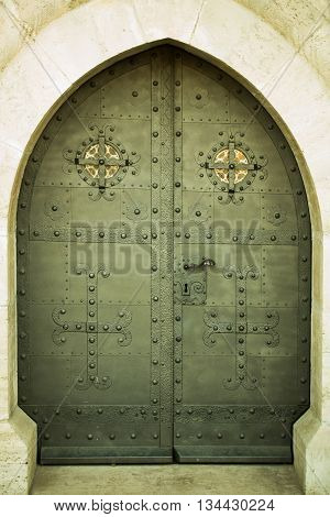 Medieval heavy strong metal door with arch gothic frame outdoor