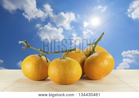 Oranges on the wooden table on the blue sky background. Fresh oranges. Oranges with sky background