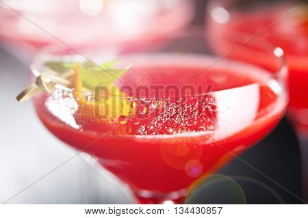 Red Alcoholic Cocktail with Raspberry Gin. Garnished with Fresh Mint Leaves and Lemon Citron