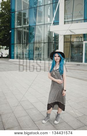 Girl With Blue Hair Dressed In Hat Grey Boho Dress, Sneakers Outdoors On Glass Building On Backgroun