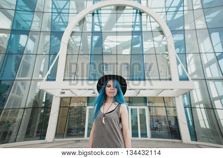 Girl With Blue Hair Dressed In Hat With Fang Necklace Outdoors On Glass Building On Background.