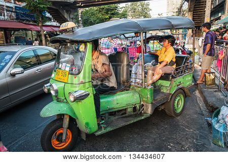 BANGKOK THAILAND - MAY 2 2016 : green thailand rickshaw tuk tuk taxi service and passenger at Huay Kwang market