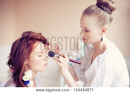Stylist makes makeup bride before the wedding