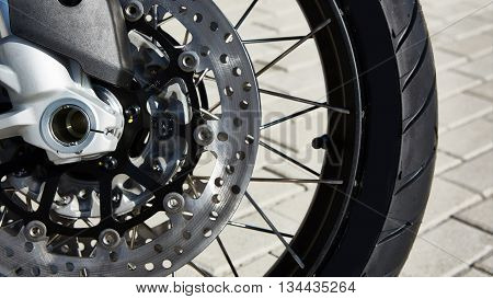 The Front motorcycle disk breaks and tire in close up