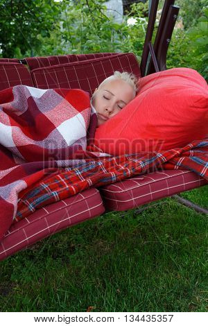 young woman slip on big soft swing in garden on red pillow covered by red checkered blank