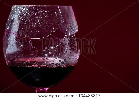 Crushed glass with red wine and water drops in studio on dark background copy space