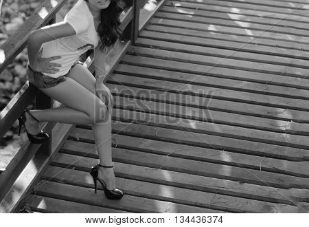 beautiful women sitting on a wooden railing.